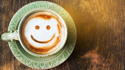 A cup of coffee with a smiley on it.