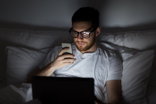 A man looking at his phone in bed.