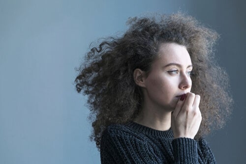 A curly-haired woman looking off into the distance thinking about dangerous words.