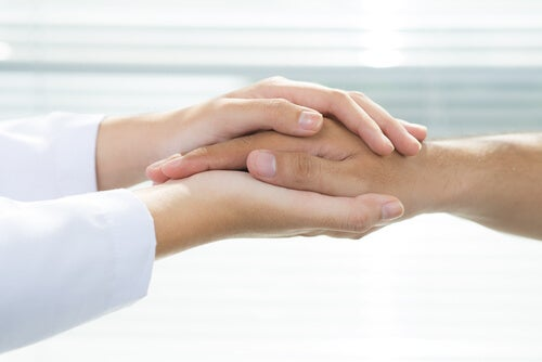 A doctor holding a patient's hands, representing universal health coverage.