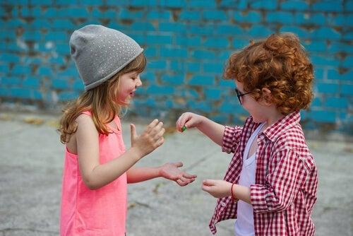 Two kids sharing treats.
