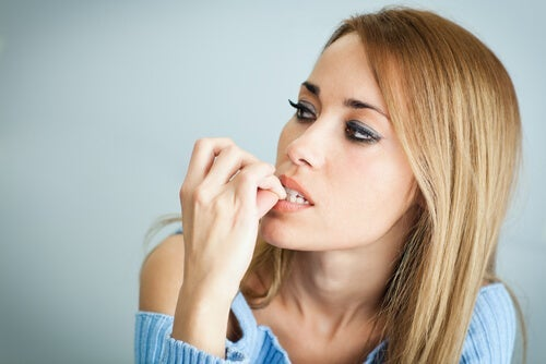 A woman biting her nails.