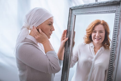 A woman with breast cancer looking at herself with hair in the mirror.