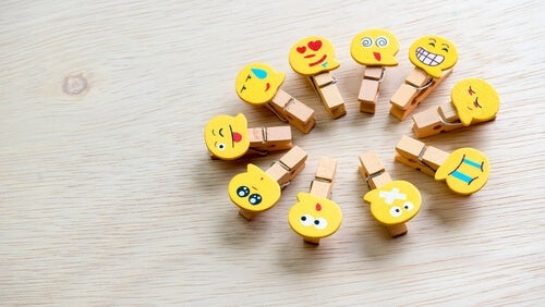 A circle of wooden clothespins with emojis on them.