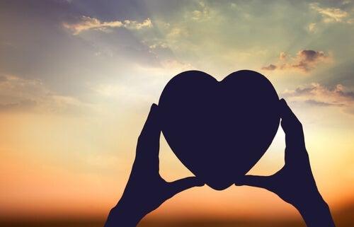 Hands holding a heart.