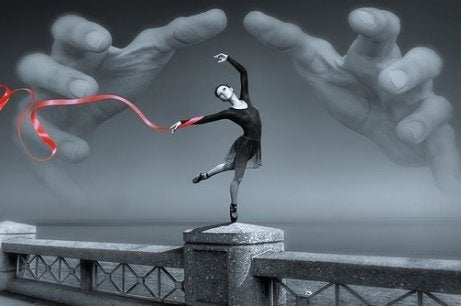 A ballerina on a bridge with giant hands about to grab her.
