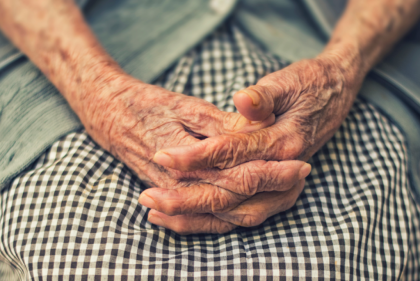 An older person's hands clasped in their lap.