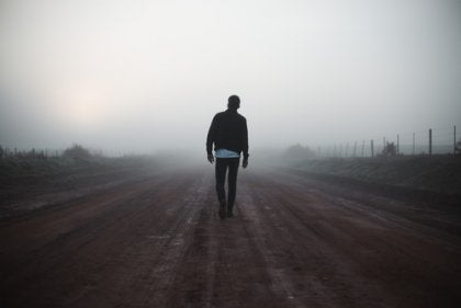 A man walking down a foggy road.