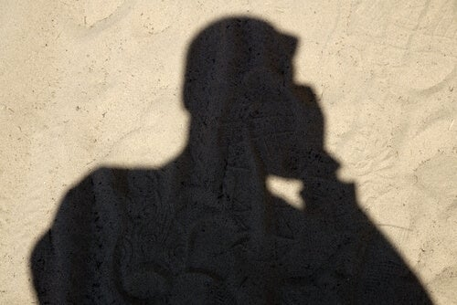 The shadow of a man talking on the phone.