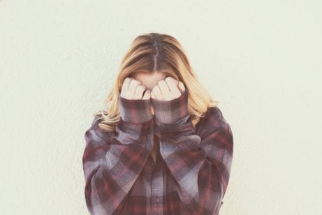 A woman covering her face with her hands.