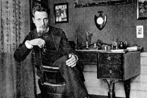 Young Rilke sitting in a desk.