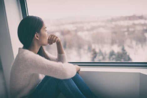 A depressed woman looking out at cloudy days.