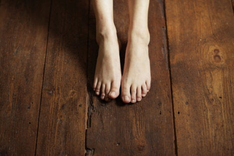 A person with their feet on a wooden floor.
