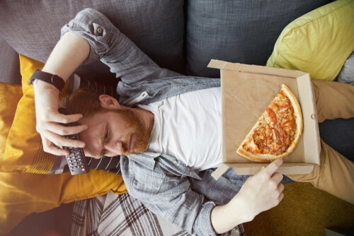 A bored man eating pizza on the couch.
