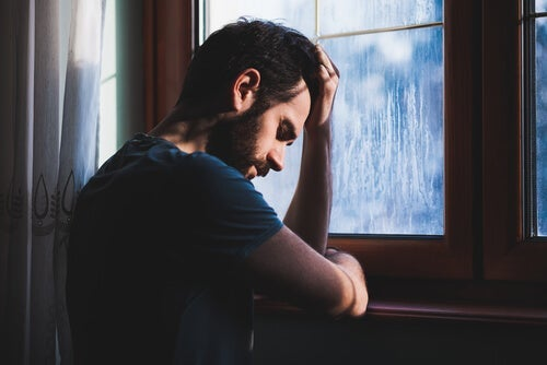 A sad man leaning up against a window.