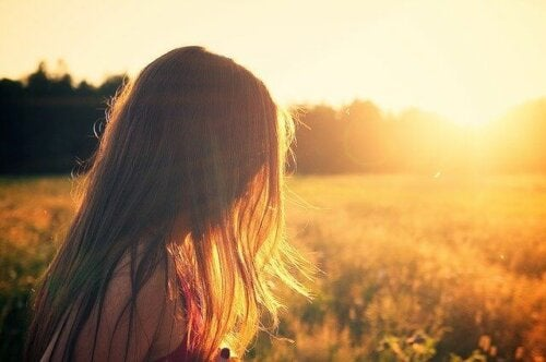 A woman in a field with the sun setting.
