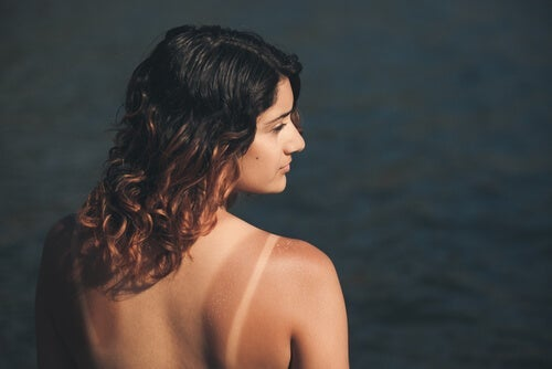 A tan woman standing in front of water.