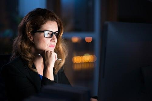 A woman staring at a computer.