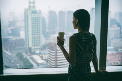 A woman drinking her coffee alone in her office.