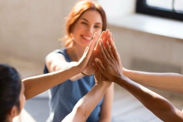 En grupp vänner gör high five.