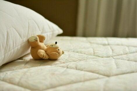 A little bear on a pillow.
