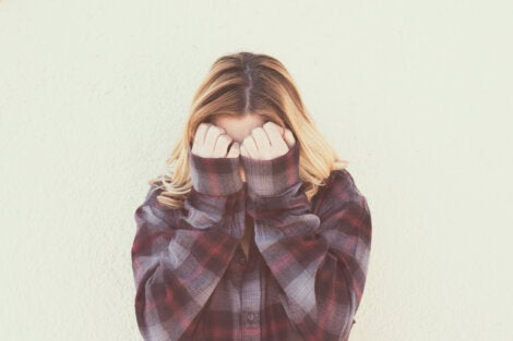 A woman covering her face.