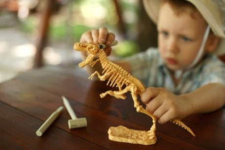A boy playing with a model dinosaur.