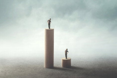 Two people standing on posts of different heights.