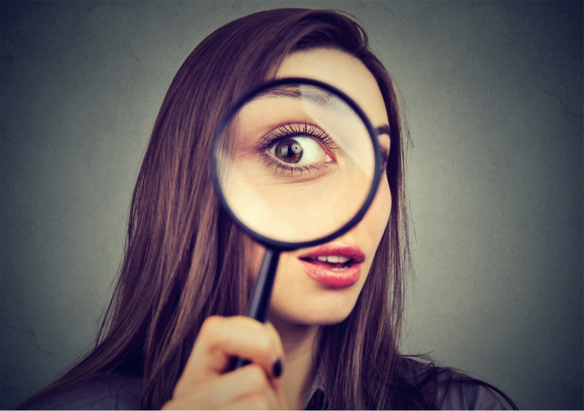 A woman with a magnifying glass.