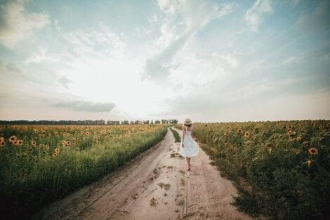 A woman walking down a dirt road.