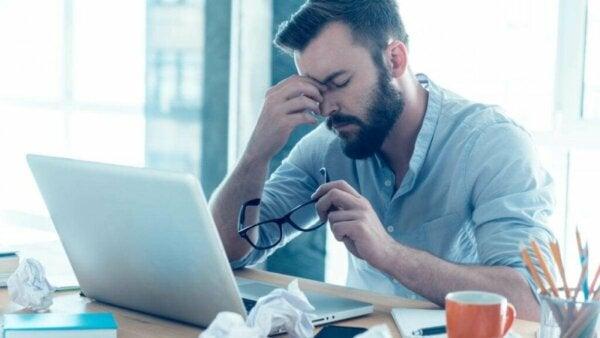 Mand ved computer oplever træthed på arbejdet