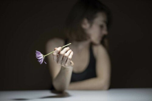 A woman holding a flower.