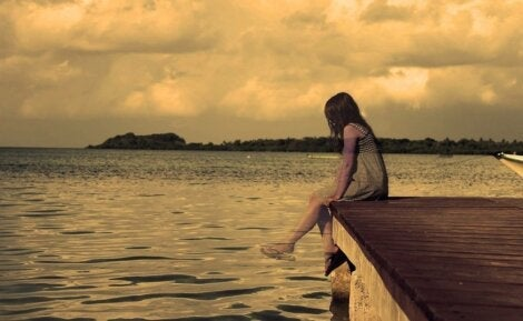 A girl sitting alone on a dock.