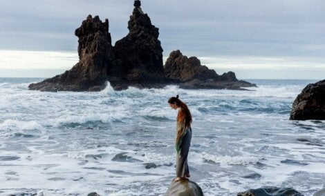 A woman standing on a rock in the ocean.