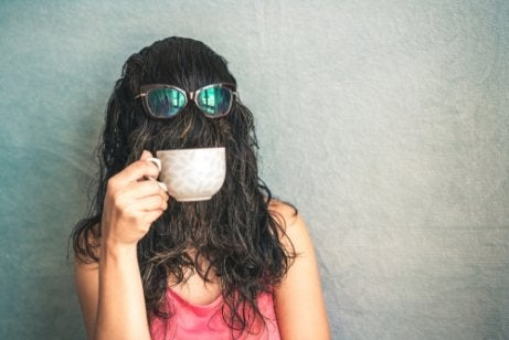 A woman with hair over her face drinking coffee.