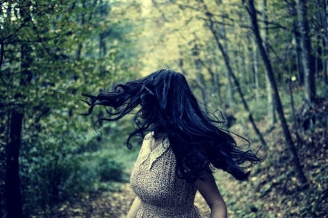 A long-haired woman running through the forest.