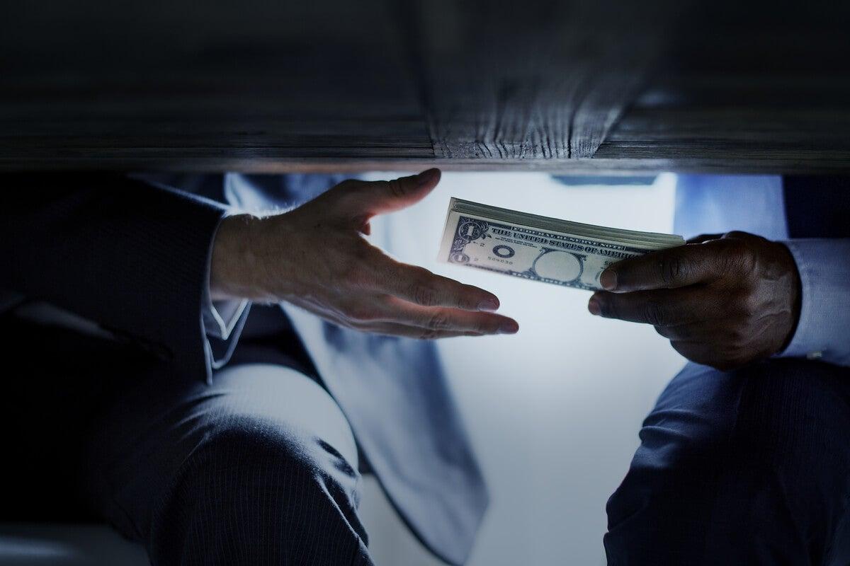A corrupt person giving money.
