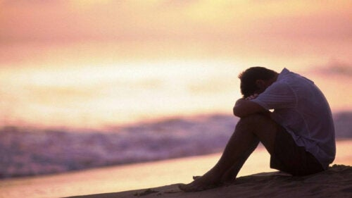 A sad man sitting by the beach thinking about extrinsic emotion regulation.