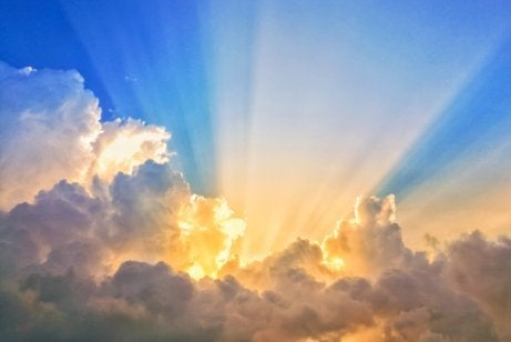 A blue sky with clouds and the sunlight.