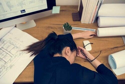 A woman sleeping on her desk.