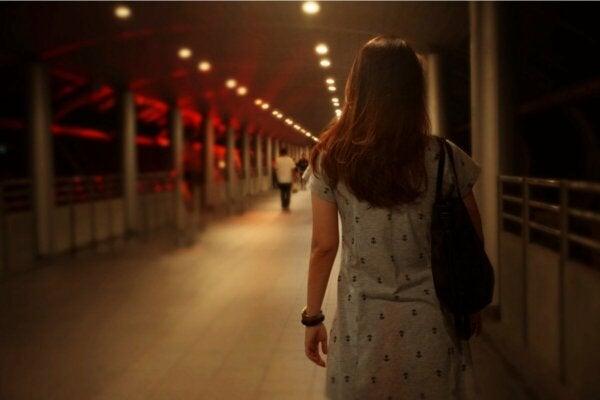 A woman crossing a bridge.