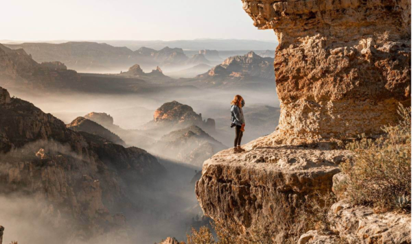 A woman standing on the edge of a cliff.