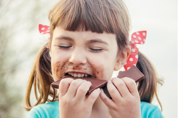 A happy girl eating chocolate, demonstrating you eat with your brain.