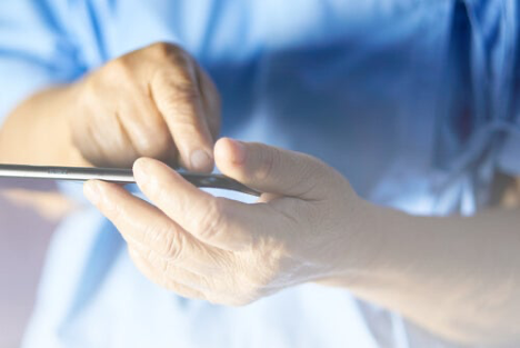 A medic using a mobile device suggesting mobile apps may help those affected by Alzheimers.