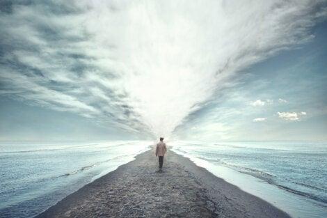 A guy walking towards the sea.