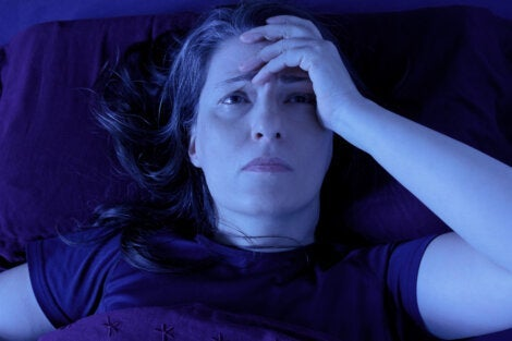 A woman in bed with a headache.