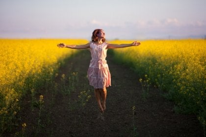 A woman walking in a country field with good self-esteem.