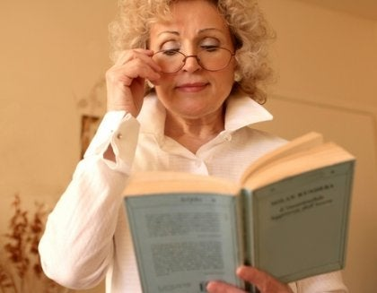 A woman with glasses reading.