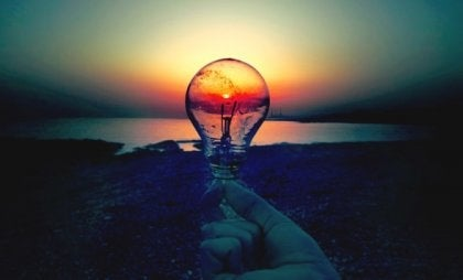 A hand holding a lightbulb in front of a sunset.