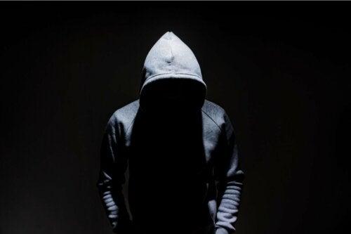 A man wearing a hoodie looking down.